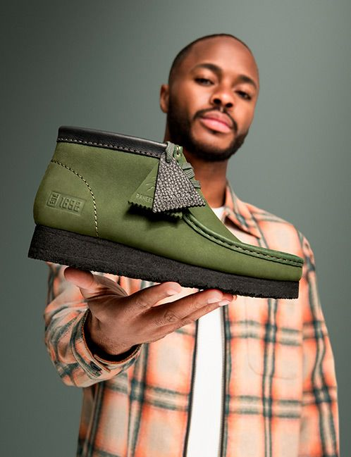 Raheem Sterling holding the Wallabee boot in khaki nubuck