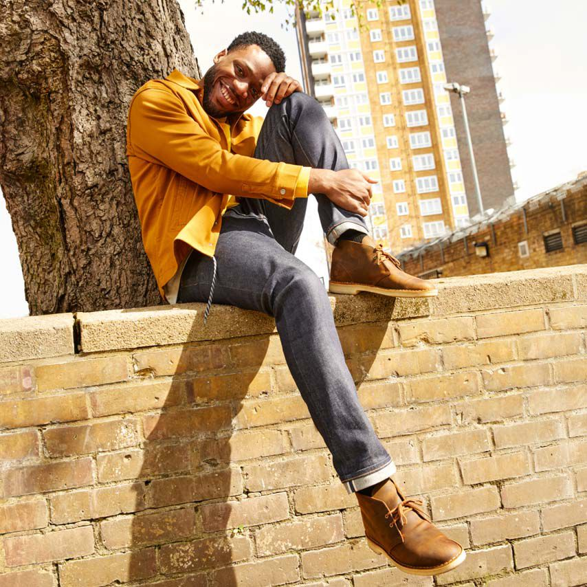 Male model sat on a wall wearing Desert Boots in brown beeswax leather