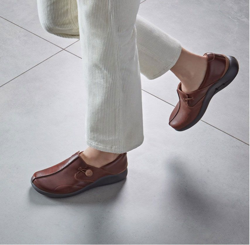 Close-up of a pair Tan Leather UnLoop Walk with a button loop fastening