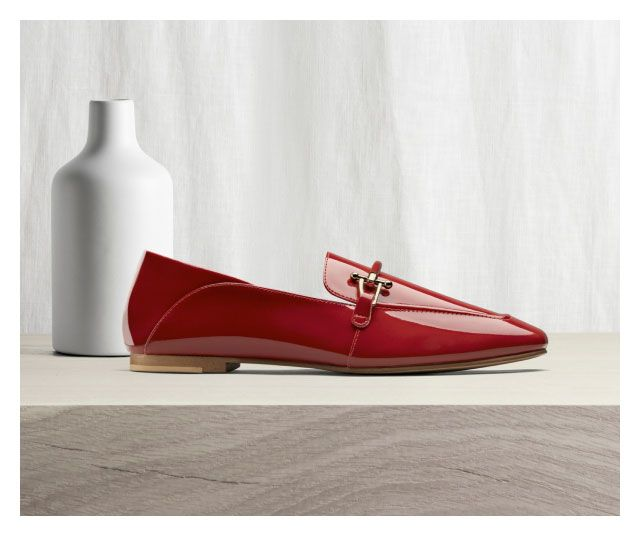 pure 2 loafer in red patent in front of a vase and curtain