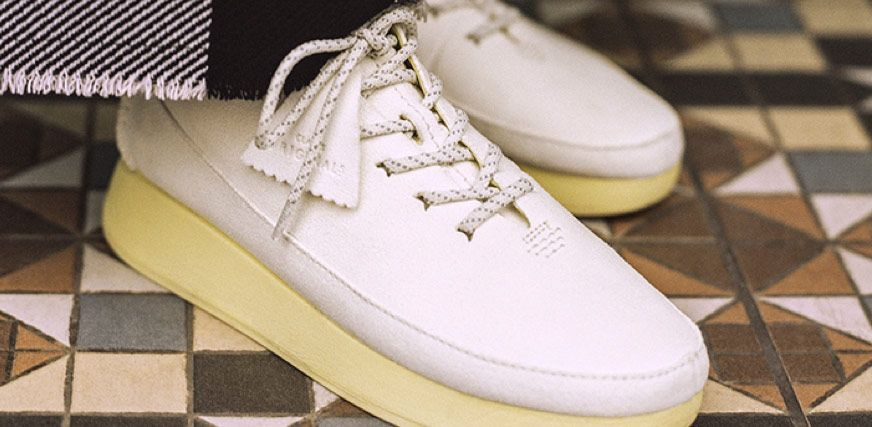 Close-up shot of a female model wearing a chunky white trainer with a pale-yellow sole