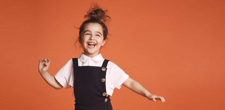 Laughing school girl wearing white school uniform shirt and black pinafore dress