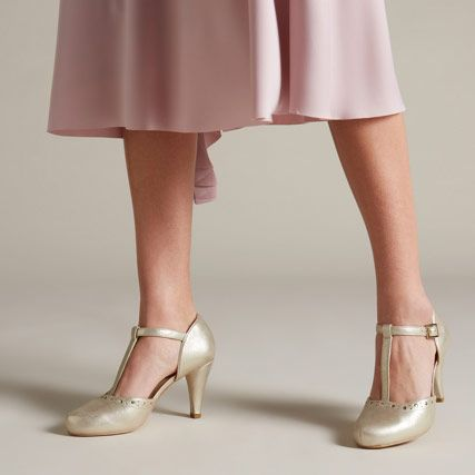 Below the waist shot of a woman wearing champagne leather high heels with brogue detailing and an ankle strap