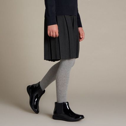 Below the knee shot of a school girl wearing black patent ankle boots with brogue detailing and lace fastening