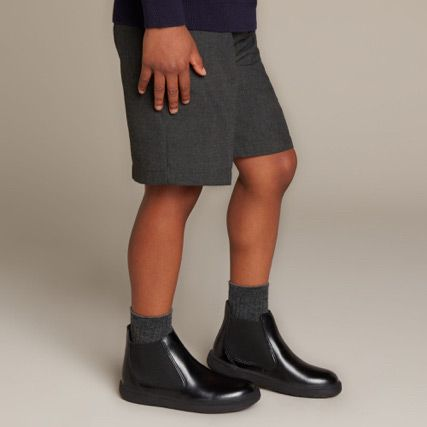 Below the knee shot of a school boy wearing black leather chelsea boots and grey school uniform shorts