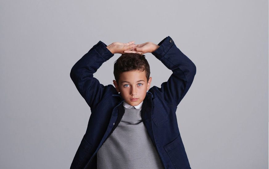 School boy wearing navy jacket and grey sweatshirt with his hands on his head