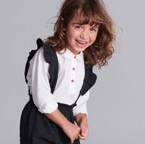 Laughing school girl in white shirt and grey pinafore dress