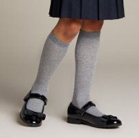 Below the knee shot of school girl wearing black leather pumps with an ankle strap and grey socks
