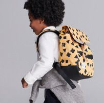 Back shot of school boy wearing a yellow patterned backpack over his shoulder