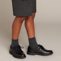 Below the knee shot of a school boy in shorts wearing black lace up school shoes