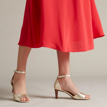 Below the knee shot of a woman wearing a metallic open toe wedding heel with a red skirt