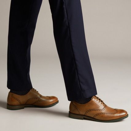 Below the knee shot of a man wearing brown leather brogue shoes with burnished detailing
