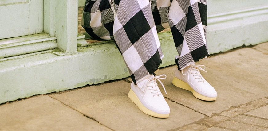 Model wearing checked trousers and white trainers
